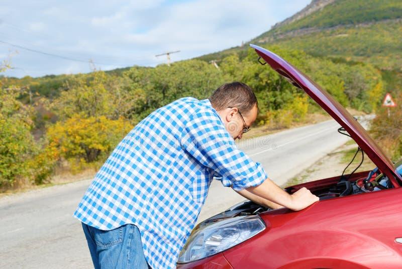 L'uomo adulto sta stando vicino alla sua automobile rotta immagini stock