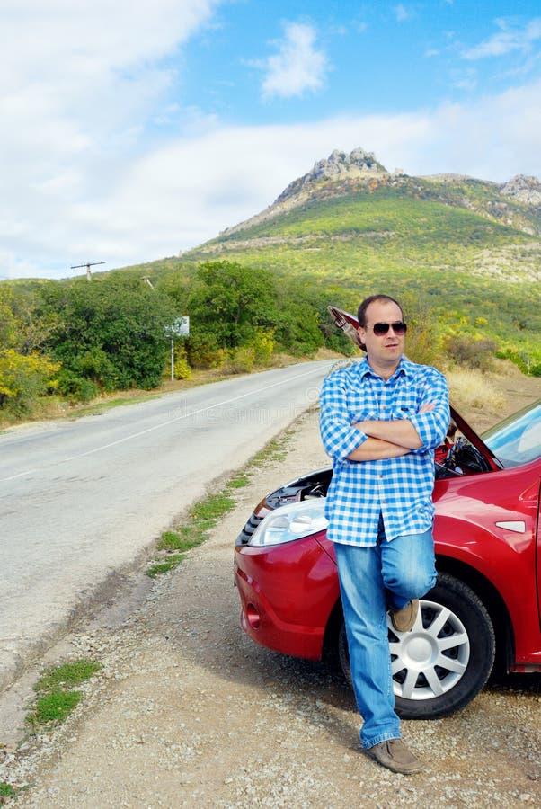 L'uomo adulto sta stando vicino alla sua automobile rotta fotografie stock