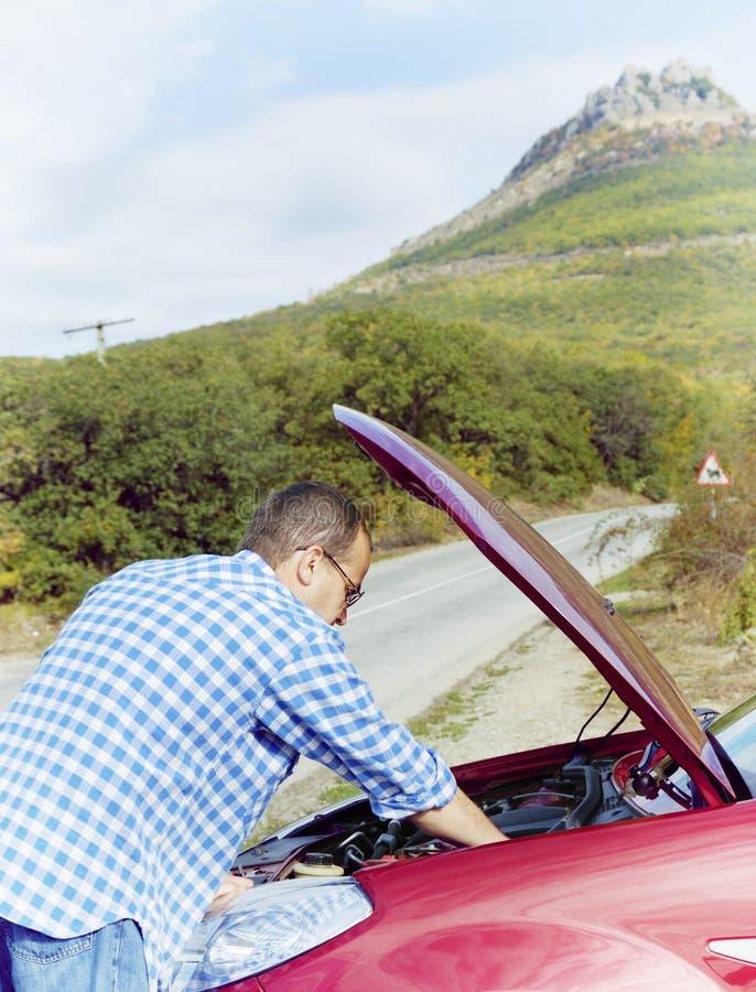 L'uomo adulto sta stando vicino alla sua automobile rotta immagine stock libera da diritti