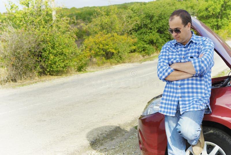 L'uomo adulto sta stando vicino alla sua automobile rotta fotografia stock
