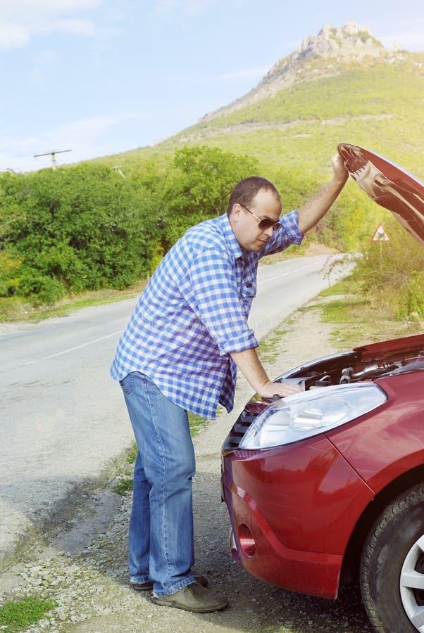 L'uomo adulto sta stando vicino alla sua automobile rotta immagini stock libere da diritti