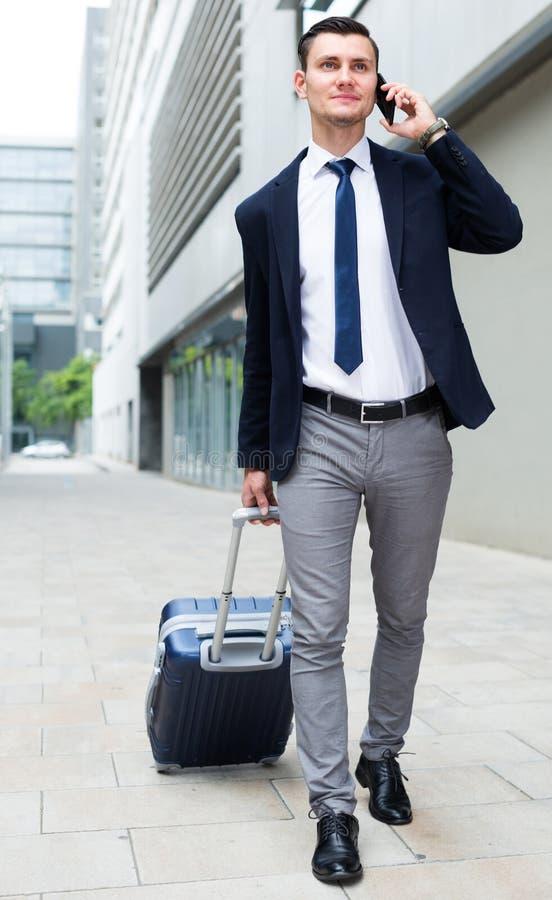 L'uomo adulto in vestito con la valigia sta parlando dal telefono fotografia stock
