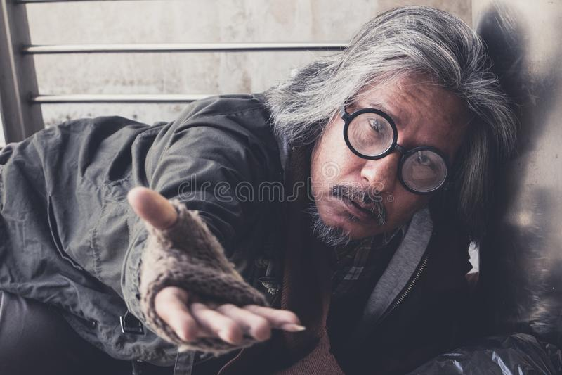 L'uomo affamato senza tetto mostrarlo per passare vuole i soldi di alimento alla via del passaggio pedonale nella città fotografie stock