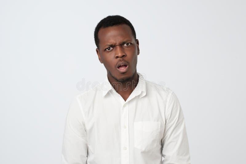 L'uomo africano arrabbiato dispiaciuto esprime le emozioni negative, isolate sopra fondo bianco immagini stock