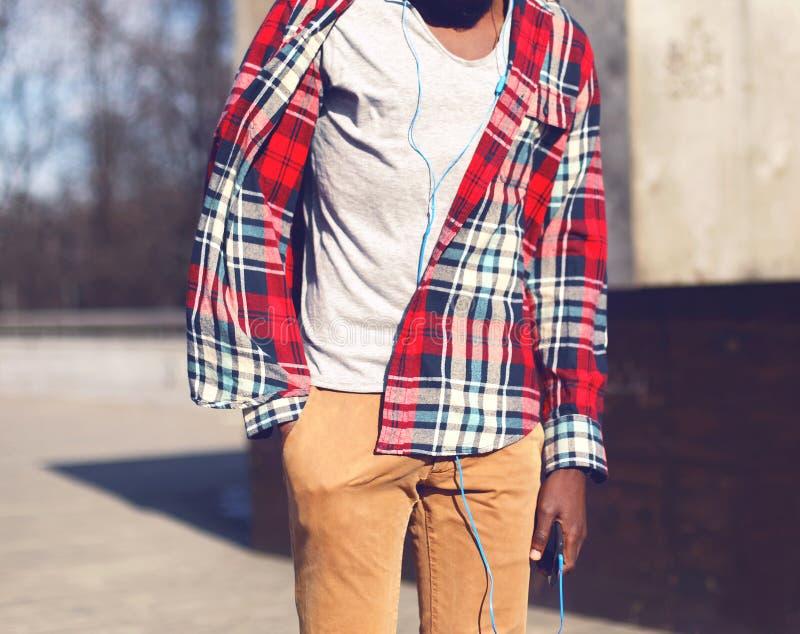 L'uomo africano di modo in camicia di plaid rossa ascolta musica fotografia stock