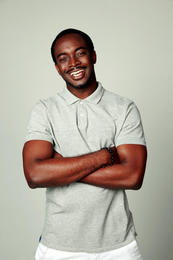 L'uomo africano felice con le armi ha piegato la condizione fotografie stock libere da diritti