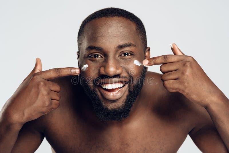 L'uomo afroamericano è spalmato di crema di fronte fotografia stock