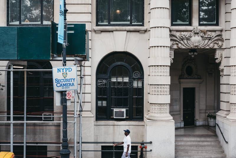 L'uomo afroamericano che cammina dalle macchine fotografiche di NYPD firma in Manhattan, New York, U.S.A. immagine stock