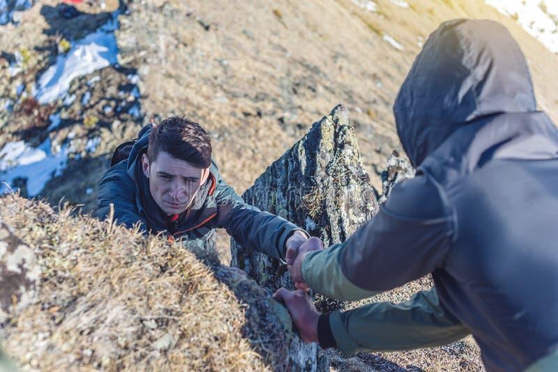 L'uomo aiuta il suo amico a scalare alla cima La viandante dà una mano per tirare su sulla montagna immagine stock libera da diritti