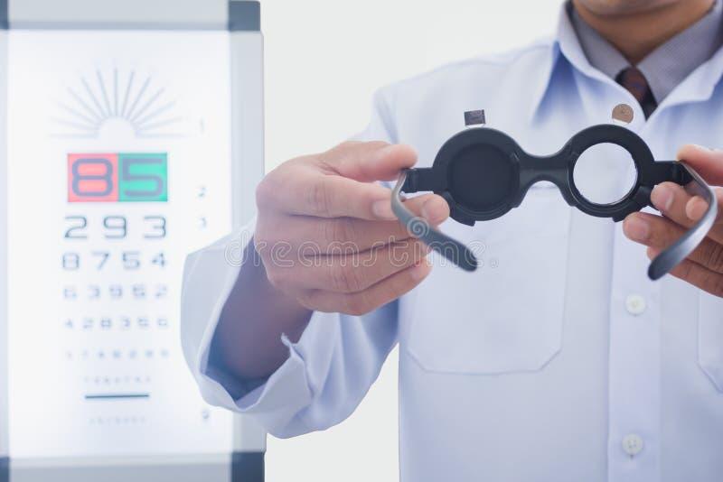 L'uomo all'ottico che tiene gli occhi ha esaminato lo strumento per mettere sul paziente fotografie stock