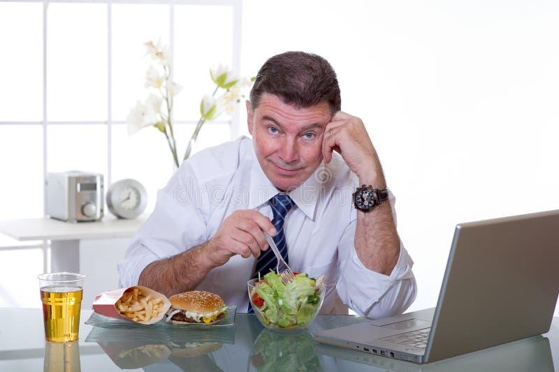 L'uomo all'ufficio mangia l'insalata verde fotografie stock libere da diritti