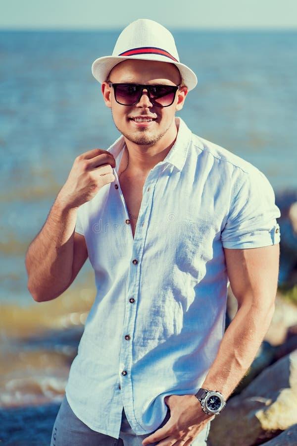 L'uomo alla località di soggiorno in camicia, occhiali da sole e cappello sui precedenti del mare fotografia stock libera da diritti