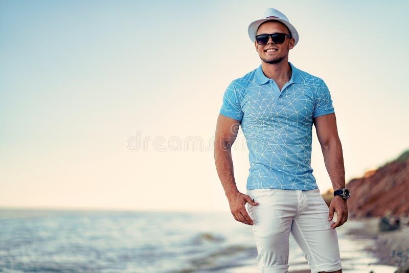 L'uomo alla località di soggiorno in un blu della camicia ed occhiali da sole, cappello sui precedenti del mare immagini stock