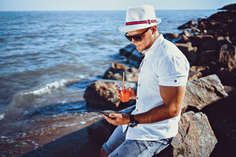 L'uomo alla località di soggiorno in una camicia ed in un cappello bianchi che si siedono su una roccia sui precedenti del mare fotografia stock