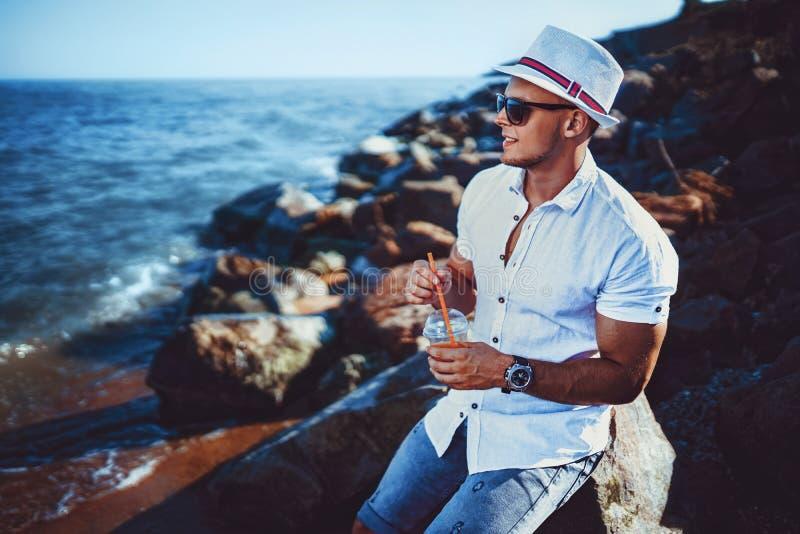 L'uomo alla località di soggiorno in una camicia ed in un cappello bianchi che si siedono su una roccia sui precedenti del mare fotografie stock libere da diritti
