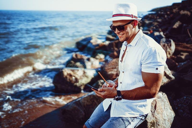 L'uomo alla località di soggiorno in una camicia ed in un cappello bianchi che si siedono su una roccia sui precedenti del mare fotografia stock libera da diritti