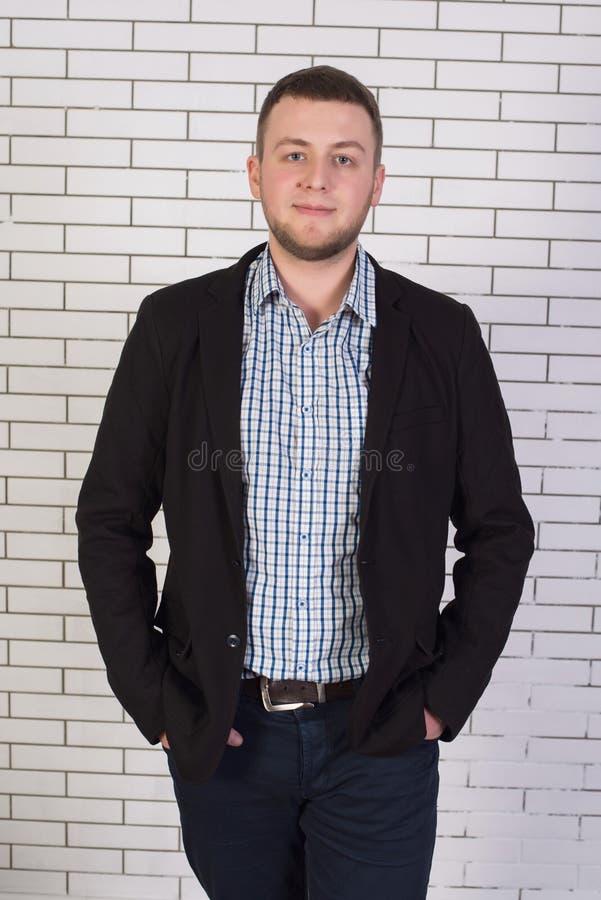 L'uomo alla moda e attraente in uno stile di affari su un fondo del muro di mattoni bianco immagini stock libere da diritti