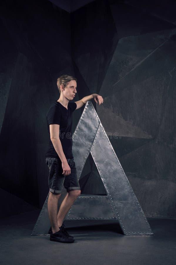 L'uomo alla moda sta vicino alla grande lettera del metallo immagini stock