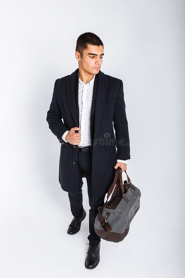 L'uomo alla moda in studio su un fondo bianco, con una borsa per il viaggio, isolata, il fondo, uomo va in viaggio immagini stock