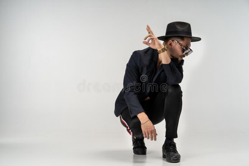 L'uomo alla moda in vestito nero ed il cappello in occhiali da sole rotondi si sono accovacciati e posare fotografie stock libere da diritti
