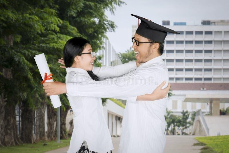 L'uomo allegro abbraccia la sua amica al giorno di laurea fotografia stock