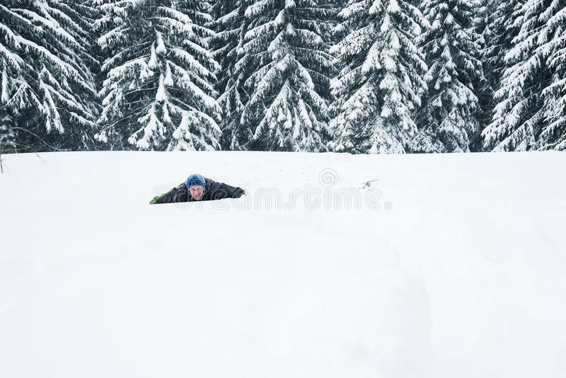 L'uomo allegro esce di una neve frana la foresta dell'inverno immagine stock libera da diritti