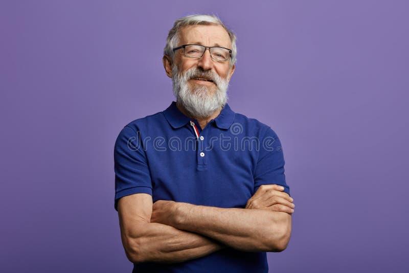 L'uomo allegro felice con il braccio ha attraversato l'esame della macchina fotografica immagine stock