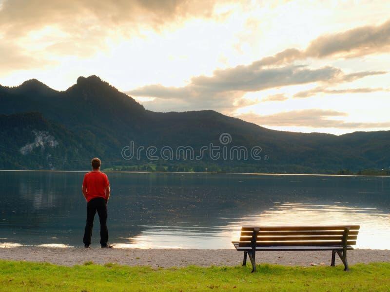 L'uomo alto in maglietta rossa al banco di legno a buio della costa del lago delle montagne si appanna fotografia stock libera da diritti
