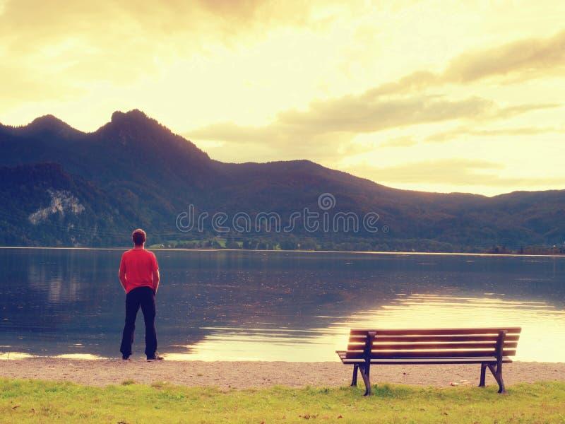 L'uomo alto in maglietta rossa al banco di legno a buio della costa del lago delle montagne si appanna immagine stock