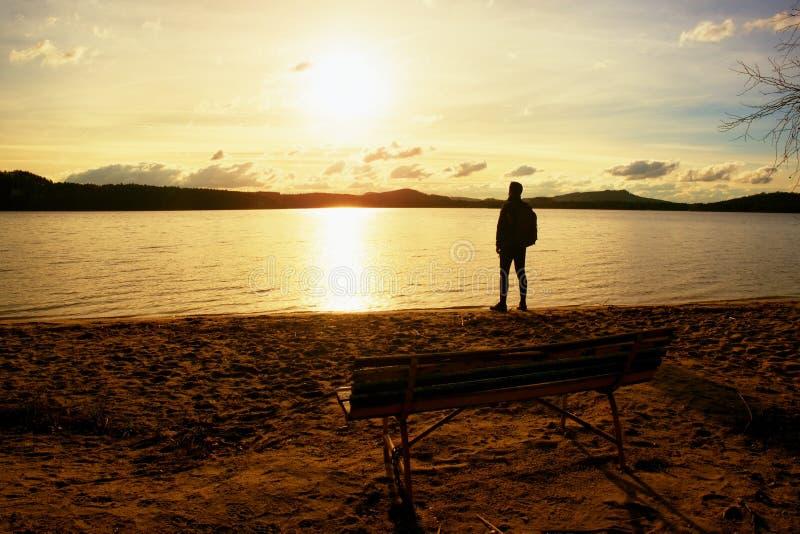 L'uomo alto va alla costa del lago vicino al vecchio banco vuoto di legno L'annata ha tonificato la foto immagini stock