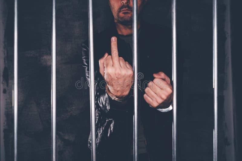 L'uomo ammanettato dietro la prigione esclude dare il dito medio fotografia stock libera da diritti