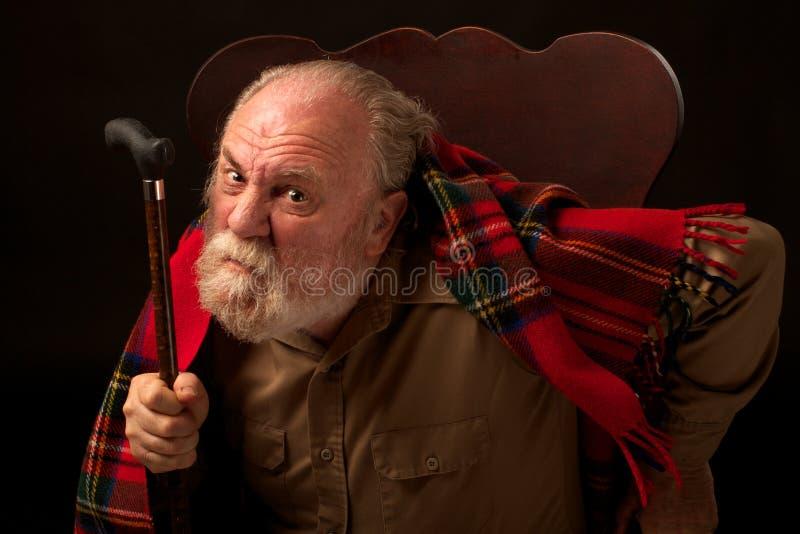 L'uomo anziano agita la sua canna ed aggrotta le sopracciglia immagini stock libere da diritti