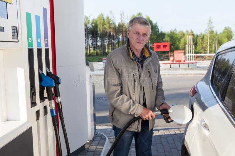 L'uomo anziano caucasico è sulla stazione di servizio con l'iniettore inserito nel pozzo del riempitore dell'automobile fotografia stock libera da diritti