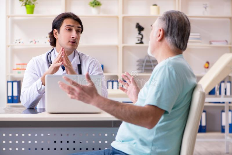 L'uomo anziano che visita giovane medico maschio immagine stock libera da diritti