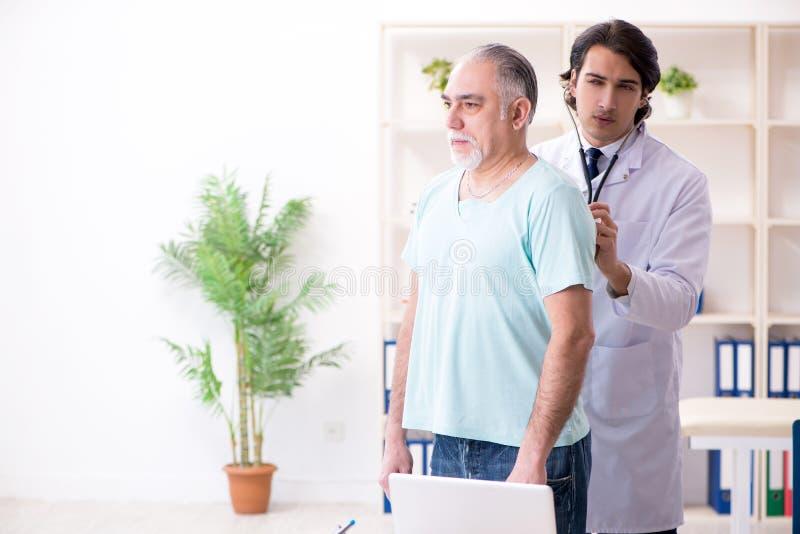 L'uomo anziano che visita giovane medico maschio fotografia stock libera da diritti
