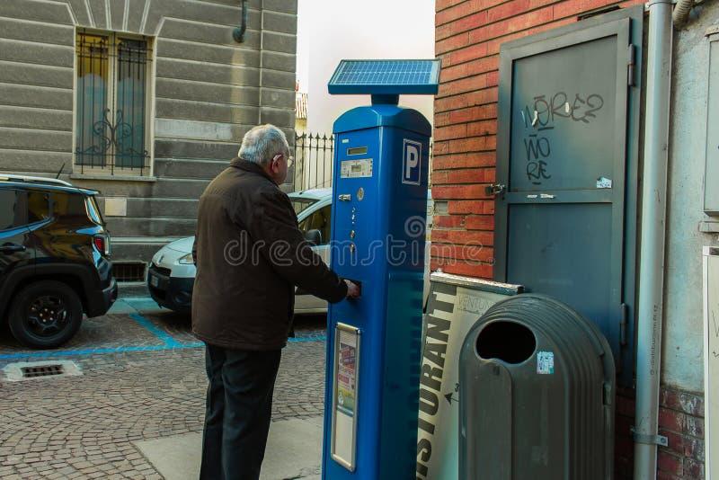 L'uomo anziano con la protesi acustica, ottiene il biglietto per parcheggio pagato dell'automobile in Italia fotografie stock