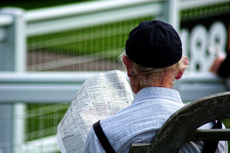 L'uomo anziano dai capelli grigio studia i corridori ed i cavalieri di corsa di cavalli fotografia stock libera da diritti