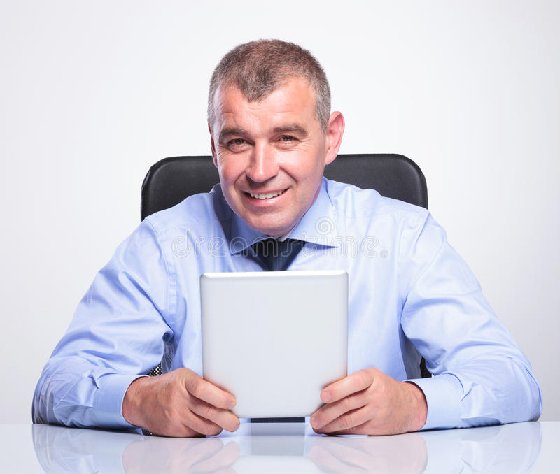 L'uomo anziano di affari allo scrittorio tiene la sua compressa fotografia stock libera da diritti