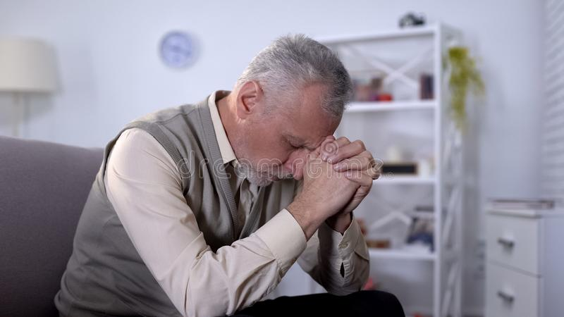 L'uomo anziano ha piegato tristemente la testa, ritenente crisi di vecchiaia sola e diminuita, fotografia stock libera da diritti