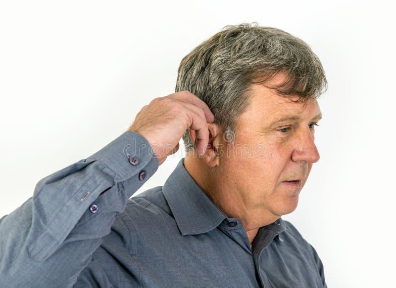 L'uomo anziano mette nella sua protesi acustica immagini stock libere da diritti
