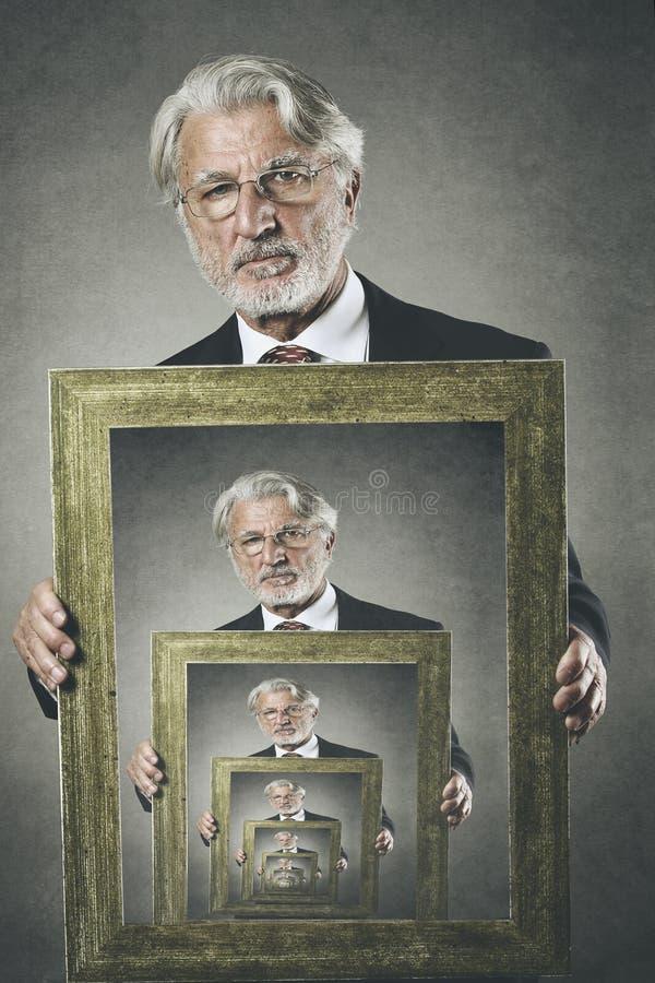 L'uomo anziano mostra il suo ritratto surreale fotografia stock