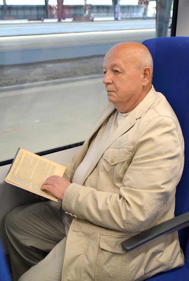 L'uomo anziano premuroso legge il libro nel vagone elettrico fotografia stock libera da diritti
