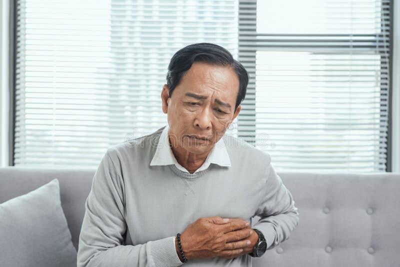L'uomo anziano ritiene il dolore nel loro cuore in salone, concetto medico fotografie stock libere da diritti