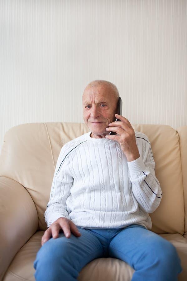 L'uomo anziano sorridente sta parlando sul telefono fotografia stock libera da diritti