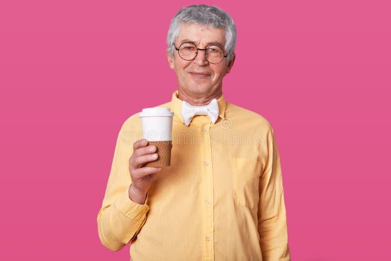 L'uomo anziano sta con coffe contro la parete rosa L'anziano giudica la grande tazza pronta per bere il baverage caldo Maschio da immagini stock
