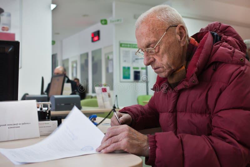 L'uomo anziano sta firmando i documenti alla banca fotografia stock