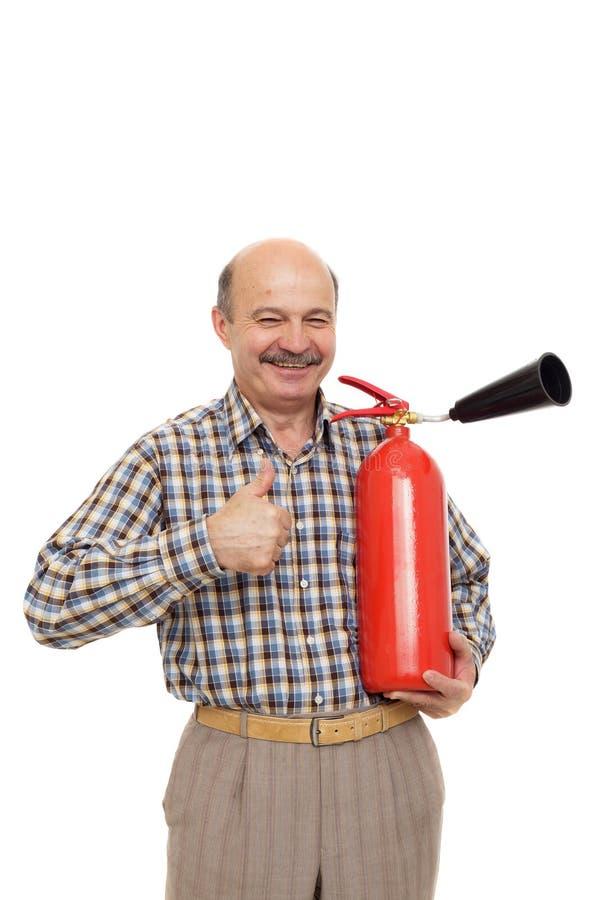 L'uomo anziano sta tenendo un estintore rosso immagini stock