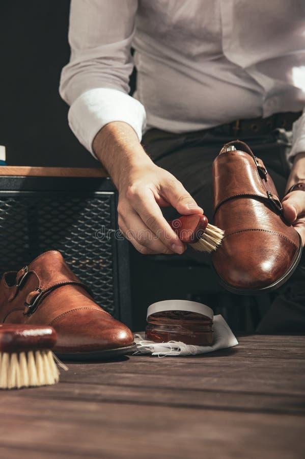 L'uomo applica il lucido da scarpe fotografia stock