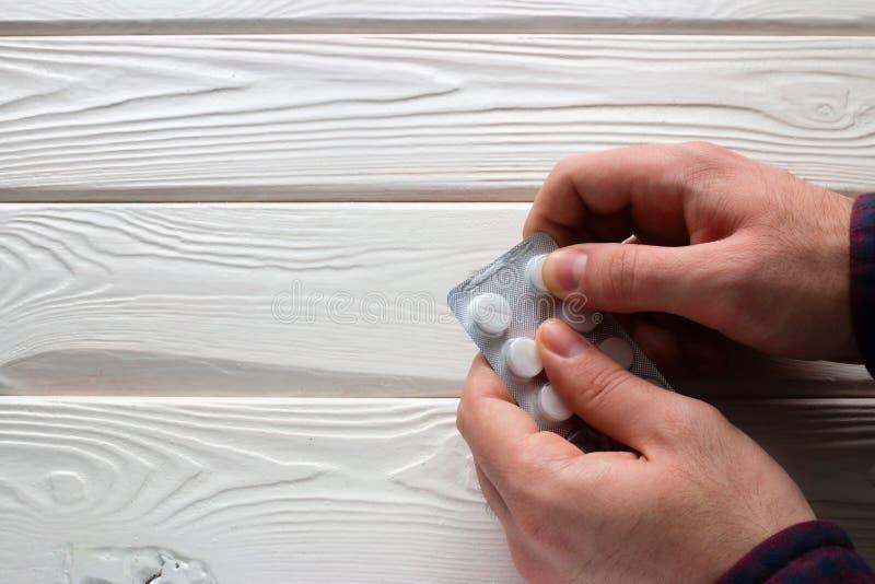 L'uomo apre un pacchetto delle pillole immagini stock libere da diritti