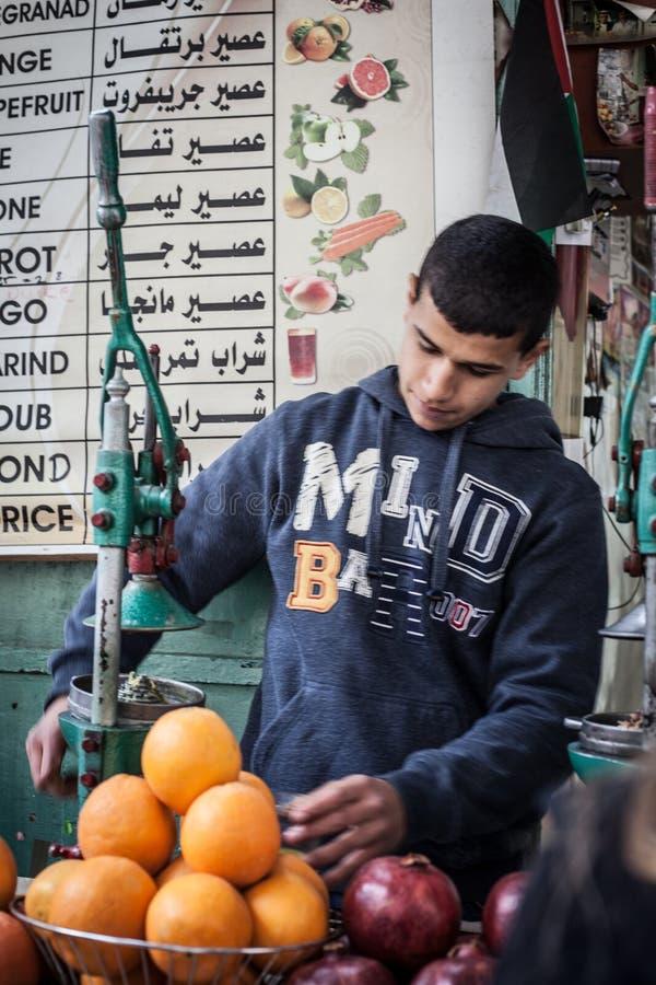 L'uomo arabo vende il succo del melograno al vecchio mercato della città di Gerusalemme immagine stock libera da diritti